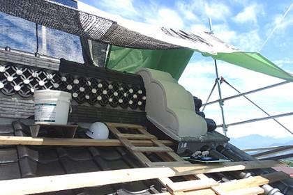 屋根の漆喰塗り工事の様子 鬼瓦の背後に影森、棟の輪違いにつなぎ止めの白円の装飾