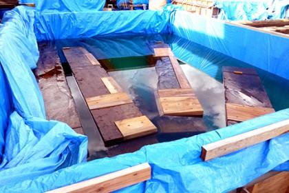 仮設の水槽に浮かべた石橋の土台
