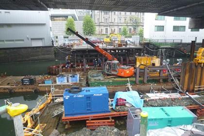 現場は石橋が取り払われ、水面に浮かぶクレーン等、基礎工事を行うためのダイナミックな仮設が