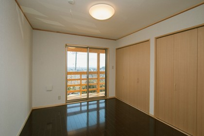 二階 寝室2 木製のバルコニーが見える