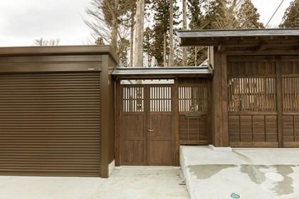 ガレージとカーポートの間に入口(木製扉)を設ける
