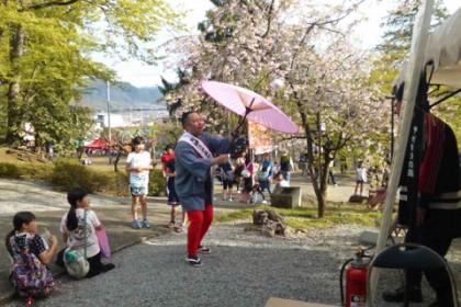 祭りの境内で太神楽の演技を披露する芸人「かがみもち」