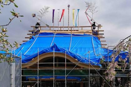 上棟式の棟飾りを装った御本堂 棟には五色の旗がひらめいて、鶴亀の鏑矢(かぶらや)が天地を射る