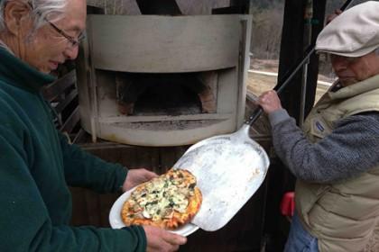 石窯からピザを取り出して…