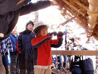 茅葺き職人の射す針に、小屋裏にいて縄を通す仕事を体験