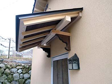 古材の持ち送りをドア上の庇に使用