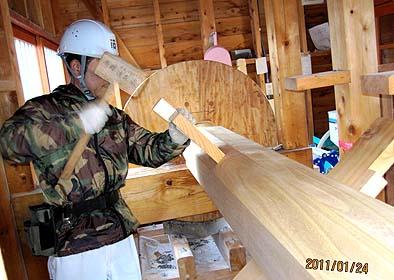 内部で精米のためのキネを持ち上げる木片を心棒に取り付ける作業
