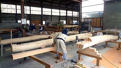 上層の小屋梁の加工風景 丸太材をチョ―ナで削り、芯からの返り墨を出して加工しています
