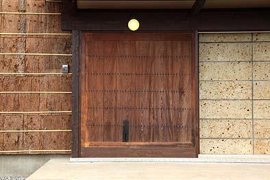 竣工・玄関戸、板張りの大戸(蔵戸)が使用されている、向かって右は大谷石の壁、左は杉皮の壁が施工されています