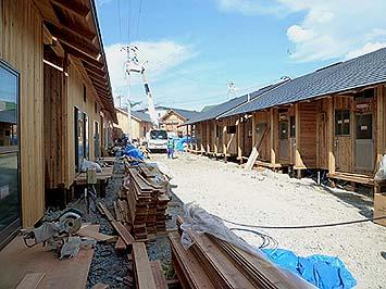 建設中の仮設住宅の家並み 庇の深いポーチや濡れ縁が道を挟んで向き合って生活感のある家並みとなっている