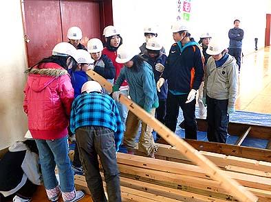 材木に書かれた番付け札を見ながら次に建て込む部材を捜す生徒たち