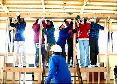 7人で力を合わせ二階の桁を柱の上にのせる