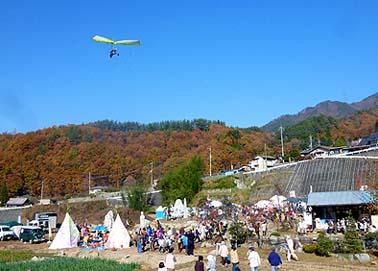 会場にハンググライダーが飛来、こども達に空からのプレゼント