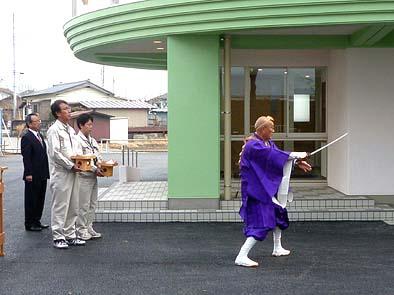 上行寺住職によって行われた仏事 供え物を持つ小柄な人物(右側)が塩野現場監督員