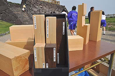 木組みや継ぎ手の模型教材、背後に本丸の石垣が見える