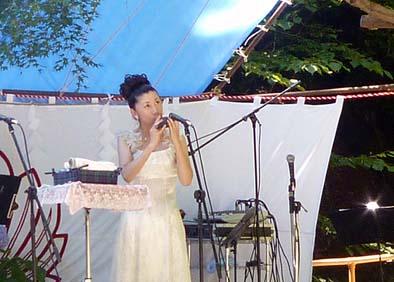 深い杜のすばらしい特設ステージでオカリナの演奏をする佐藤一美さん、大嶽山那賀都神社とは少なからぬ縁があるという。