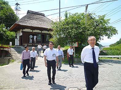 集落内を散策される横内知事、背後に茅葺きの観音堂が見える