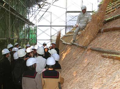 文化財建造物保存技術協会の丸本所長から茅葺きの講義を受ける生徒たち