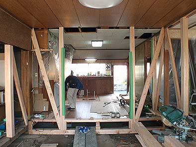 工事中 居間よりダイニングキッチン方向を見る。耐震壁には新たに土台を入れ、土台から桁にかけて筋違を構造上有効に設置した。