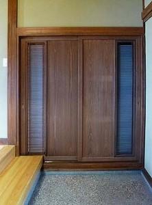 玄間の靴収納。古い欄間を利用した扉。