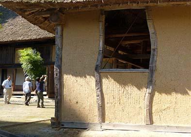馬屋の南側の窓。弓なりに曲がった栗の木の柱と荒壁が特長的です。奥に見えるのは主屋。