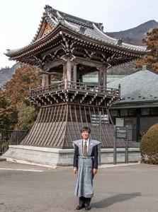 社長が初めてつけた裃(カミシモ)、昨年暮れ修復が完了した「時鐘(トキノカネ)」の前にて。