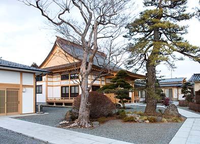 向かって中央に本堂、左に客殿、右に書院。中庭に山号「岩松山」にちなんだ岩と松が見える
