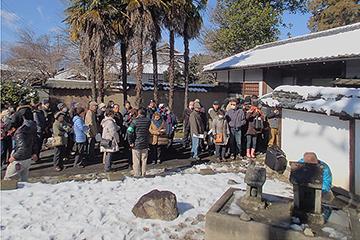 開場を待ちかねて屋敷の長屋門前に並ぶ人々