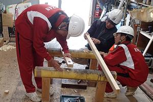 大工道具のノミを持って、木材に穴堀の体験
