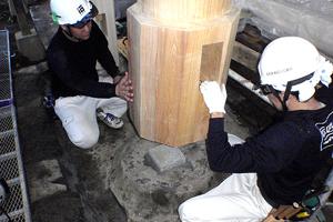 据え直した亀腹状の台石の上に修理を終えた柱を立てる