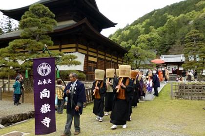 虚無僧の一団を先頭に仏殿前を進む稚児行列