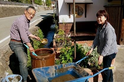 棟梁の家の花壇で作業する、青柳茂さんと植田眞美さん