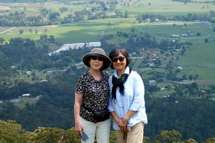 かづ美さんと順子さん 背景はブリスベン近郊の広大な農場地帯